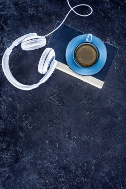 top view of book, white headphones and blue cup with coffee on grey tabletop