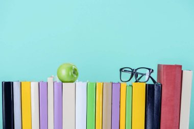 row of books with apple and glasses isolated on blue