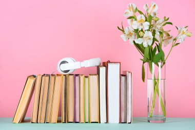 headphones on row of books and flowers in glass on table