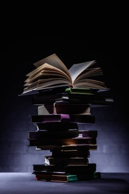 stack of books with open book on top on dark surface