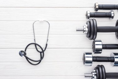 top view of various dumbbells and stethoscope on white wooden surface
