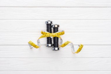 close-up view of dumbbells and yellow measuring tape on wooden surface