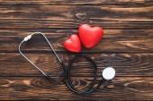 pohled shora symbolu srdcí stetoskop a červené na dřevěný stůl