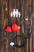 Photo top view of white figures of family holding hands, red hearts symbols and stethoscope