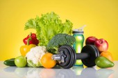 Photo close-up view of dumbbell, bottle of water and fresh fruits and vegetables on yellow