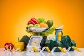 čerstvé ovoce a zelenina na váhy, sportovní láhev s vodou, činky a měřicí páska žlutá