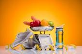 Fotografie Nahaufnahme von frischem Obst und Gemüse auf Skalen, Sport-Flasche mit Wasser, Turnschuhe und ein Maßband auf gelb