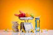 Detailní pohled čerstvého ovoce a zeleniny na váhy, sportovní láhev s vodou a měřicí páska žlutá