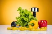 friss zöldségek, szalag és súlyzók sárga kiadványról