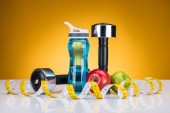 Photo close-up view of dumbbells, measuring tape, bottle of water and apples on yellow