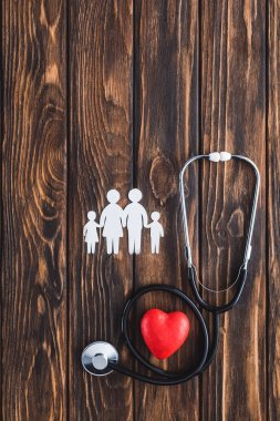 top view of white figures of family holding hands, red heart symbol and stethoscope on wooden table
