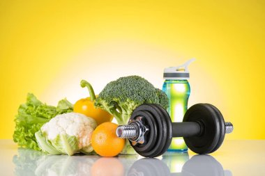dumbbell, bottle of water and fresh orange and vegetables on yellow