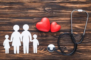 top view of white figures of family holding hands, red hearts symbols and stethoscope on wooden table top