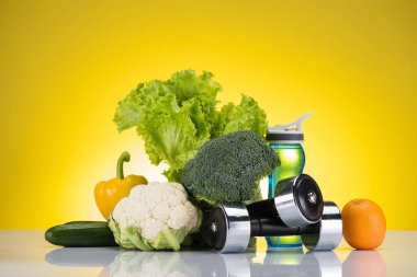 fresh healthy vegetables, orange, dumbbells and bottle of water on yellow