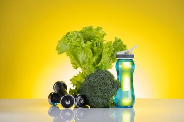 fresh green vegetables, bottle of water and dumbbells on yellow