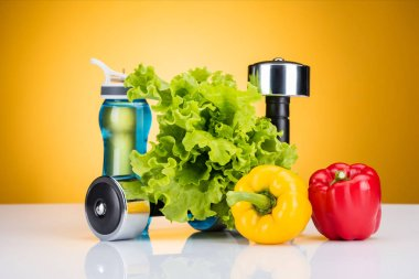 close-up view of dumbbells, fresh vegetables and bottle of water on yellow