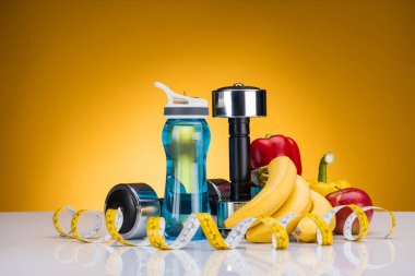 close-up view of dumbbells, bottle of water, measuring tape and peppers with fruits on yellow