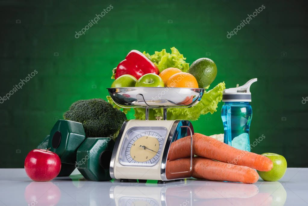 close-up view of fresh fruits and vegetables on scales, dumbbells and bottle of water on green