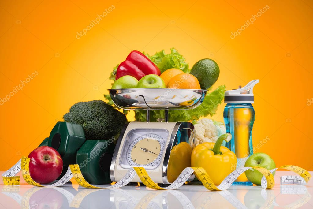 Close-up view of fresh fruits and vegetables on scales, sports bottle with water, dumbbells and measuring tape on yellow