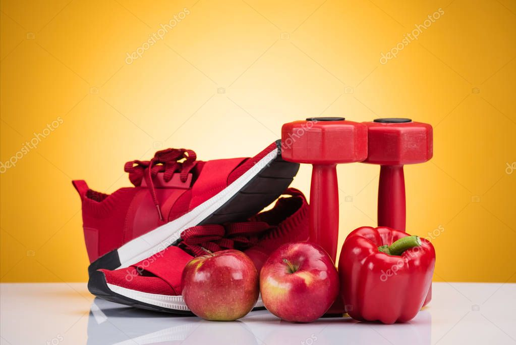 Close-up view of red sneakers, apples, pepper and dumbbells on yellow