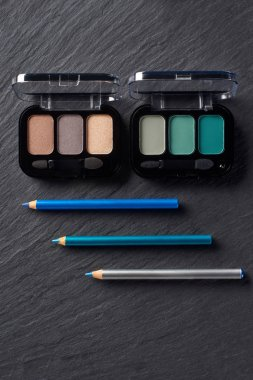 Eye shadows palettes and blue eye pencils on dark slate background