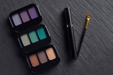 Makeup palettes with mascara and brush on dark slate background