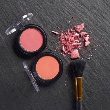 Broken blush by pressed blush with brush on dark slate background