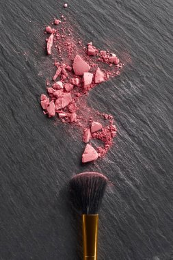 Broken blush and large brush on dark slate background