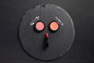 Set of blush and lipstick on round slate background