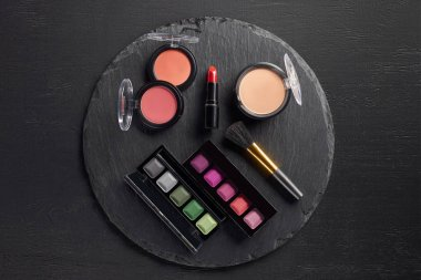 Makeup set with eye shadows and lipstick on round slate background stock vector