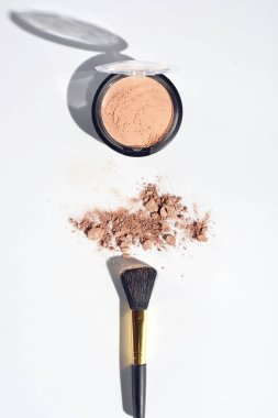 Scattered face powder with brush on white background