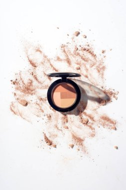 Scattered powder and contouring product on white background