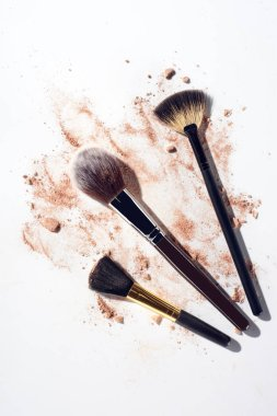 Broken face powder pieces and makeup brushes on white background