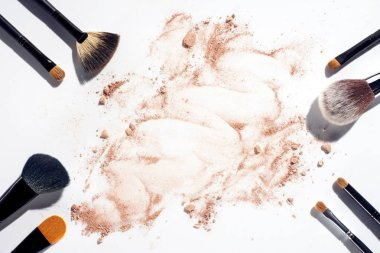 Frame of makeup brushes on white background with scattered face powder