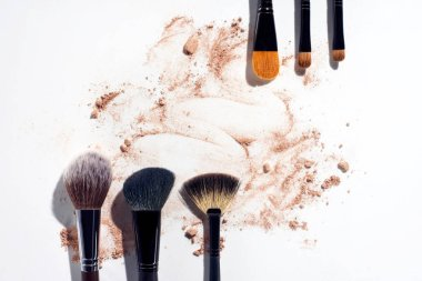 Frame of makeup brushes with powder foundation on white background stock vector
