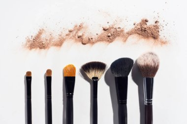 Line of scattered face powder and makeup brushes on white background
