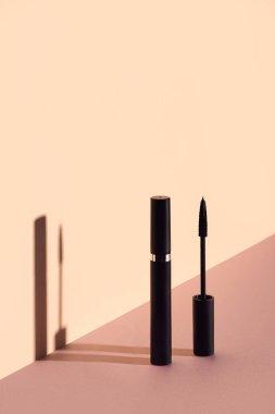 Single mascara tube with brush on beige background