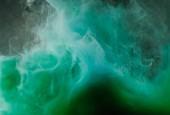 abstraktní tekoucí bílý, zelený a modrý inkoust na černém pozadí