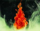 Detailní pohled rozpadu světlé abstraktní oranžovou barvou na černém pozadí