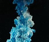 Nahaufnahme abstrakter, blau und weiß fließender Farbe auf Schwarz