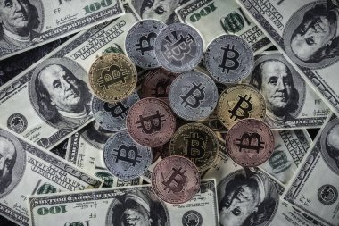 top view of pile of various bitcoins on dollar banknotes