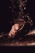 Fotografia Chiuda sullimmagine di cioccolato fondente grattugiato che cade su pezzi di cioccolato su priorità bassa nera