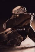 Fotografia primo piano ha sparato di organizzato pezzi di cioccolato fondente sulla tavola di legno su priorità bassa nera