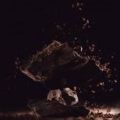 Detailní záběr záběr strouhané čokolády pádu na připravené kousky čokolády na černém pozadí
