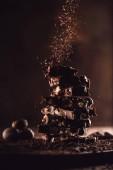 Fotografia Chiuda sul colpo di noce moscata e cioccolato grattugiato che cade sulla pila di pezzi di cioccolato sulla tabella di legno