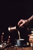 oříznutý obraz žena nalévání kávy z Turku do šálku u stolu s čokolády, pralinky, svíčky a kávové zrna na černém pozadí