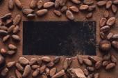 Fotografia vista elevata di superficie vuota circondata di fave di cacao ricoperto di cioccolato grattugiato