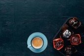Pohled shora lahodné muffiny s polevou a modré šálek kávy na dřevěné pozadí