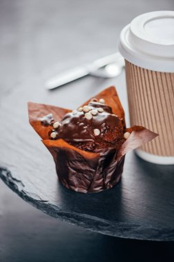 Sweet chocolate muffin with coffee cup on slate board