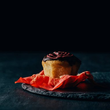 Sweet muffin with chocolate icing on slate board